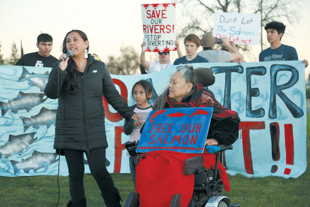 "A woman standing at mic, with child beside her, and an elder woman in a wheelchair holding a painted sign reading ""Free our Salmon"" Students hold a banner behind them reading ""No More Water for Profit!"""