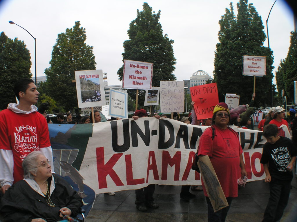 "Protestors holding sign reading ""Un-Dam the Klamath"""