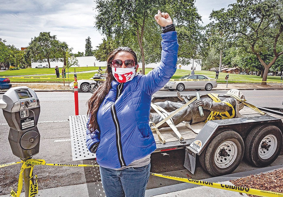 image of woman standing with fist raised and face mask on in front of a statue of John Sutter laying down, tied to a truckbed to be hauled away.