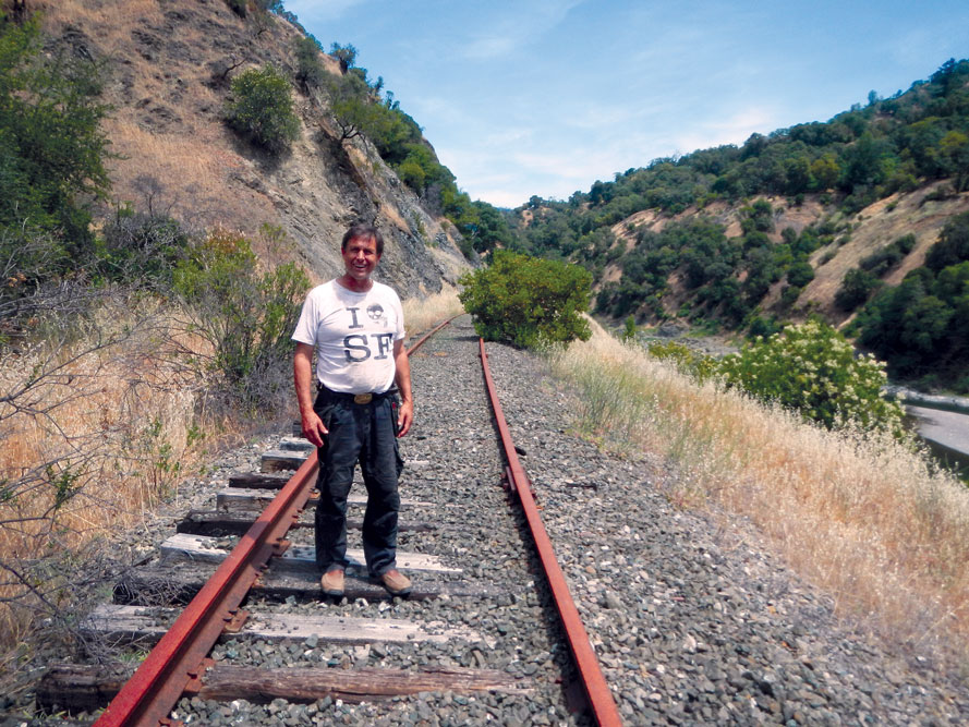 Mid-Eel Watershed Steward Mickey Bailey stands on the decommissioned railroad track that will become part of the Great Northern Redwood Trail, running through his property along Woodman Creek. They also work to create Fire-Resistant Forests.